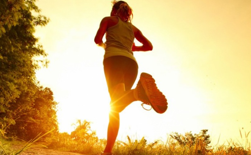 lifestyle image of person running into the sun set