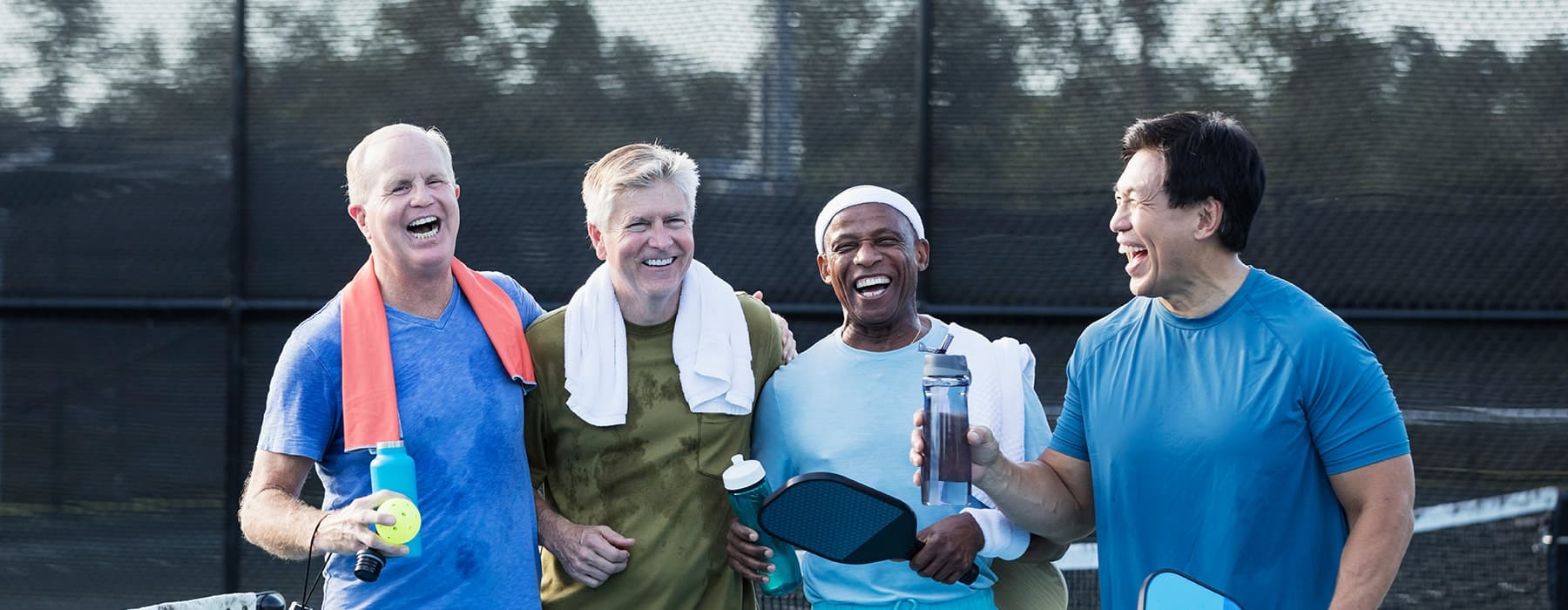 lifestyle image of four men laughing at a tennis court