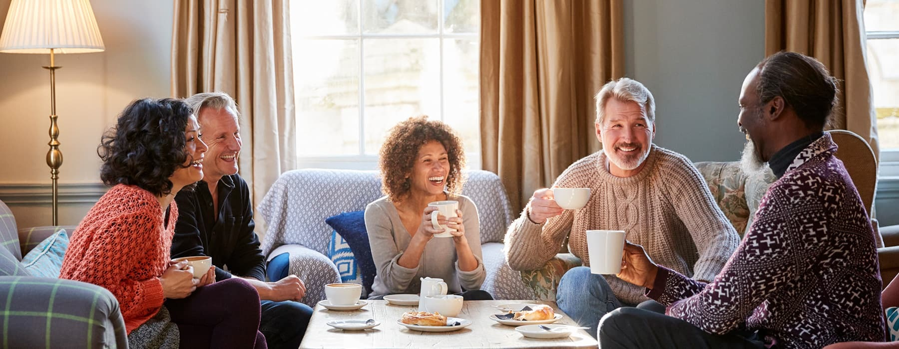 lifestyle image of a group laughing and talking on a couch