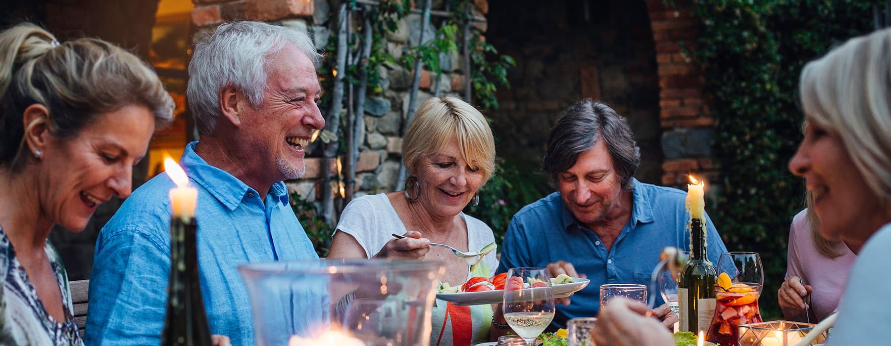 lifestyle image of a group of people laughing over a meal